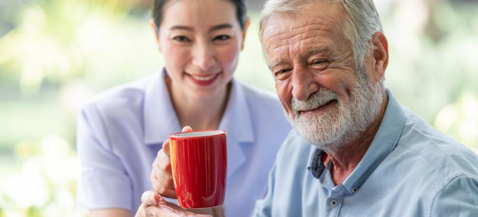 Älterer Herr und Krankenpflegerin halten eine Tasse Kaffee in den Händen.